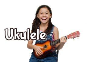 happy kid playing ukulele